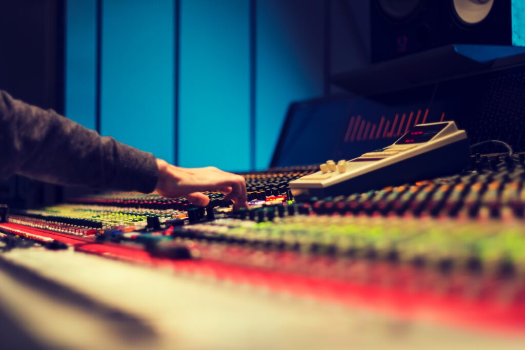 A sound engineer mixing a song on an analogue console.